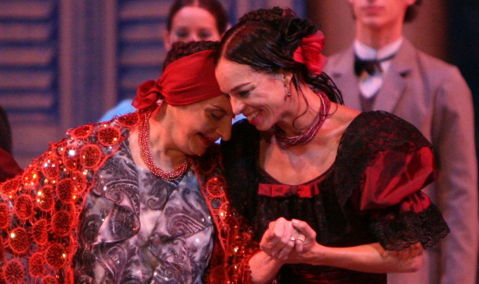 Alicia Alonso smiles as she tips her head to touch her forehead to Vald\u00e9s' temple. Vald\u00e9s, also smiling, grasps Alonso's hand with her own. Alonso is in fancy clothes in reds and grays, with one of her signature headbands. Vald\u00e9s is in a black and red costume with poofy sleeves.