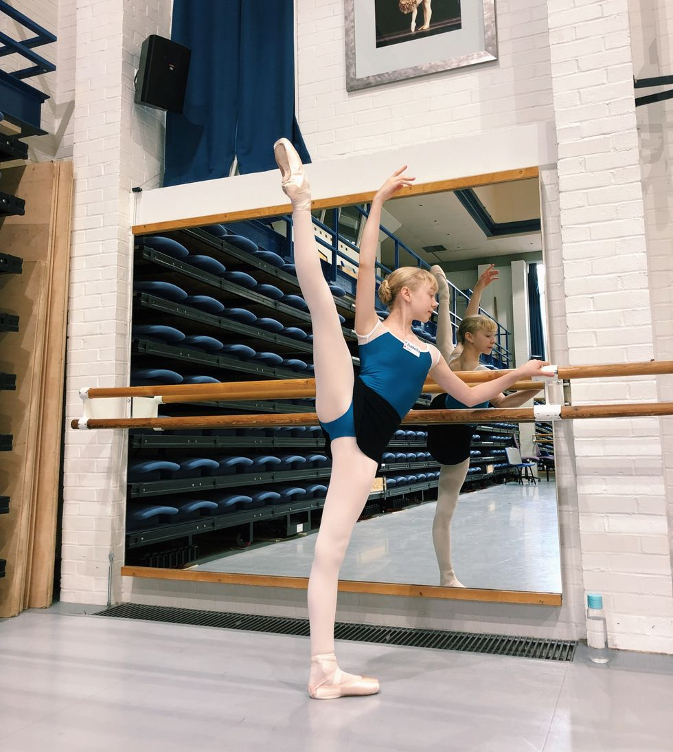 A teenage ballet student in a blue leotad, pink tights, skirt and pointe shoes poses with her right leg lifted high to the side.