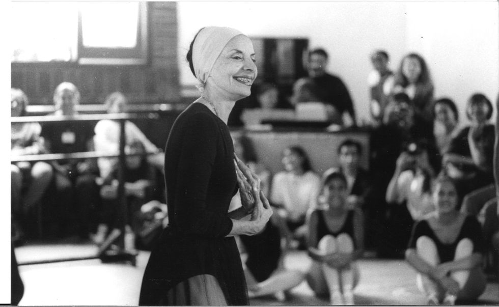 Alicia Alonso, in a long=sleeved black leotard, dark tulle skirt, and headband smiles at out of focus dancers and spectators seated around her as she stands in the middle of a ballet studio.
