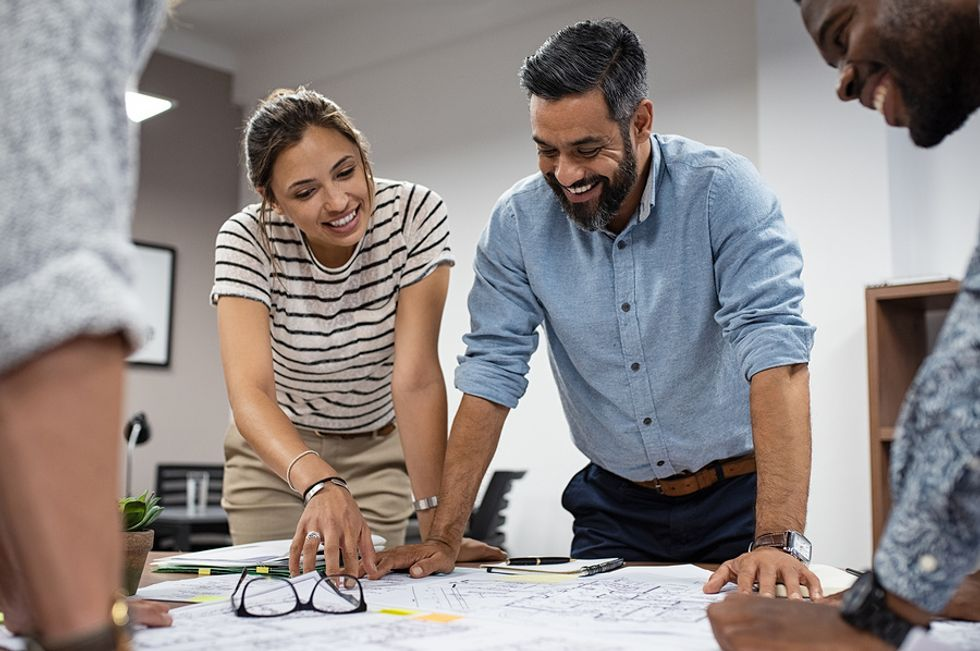 Professional man and professional woman smiling while going over a work project they are passionate about.