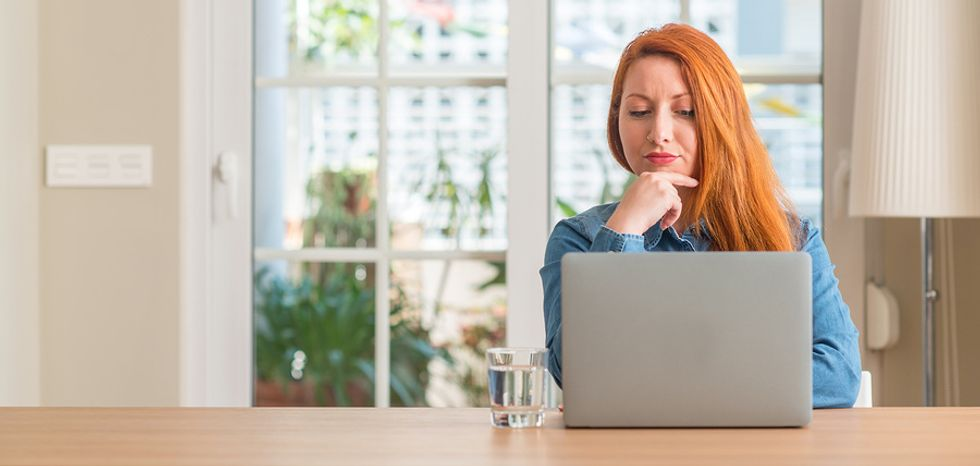 Professional woman sitting at her home laptop, wondering if the career she wants to pursue is realistic.