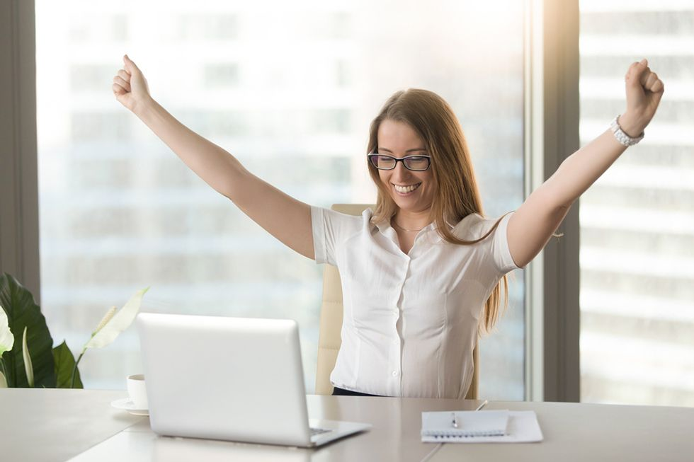 Young professional woman cheering in excitement at her desk because she's excited to be working a job she's passionate about.