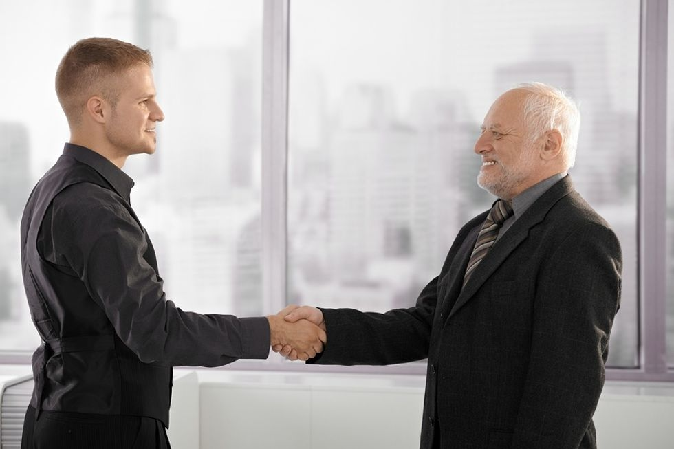 Young professional man shaking hands and networking with an older executive man in an office.