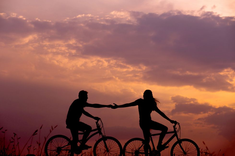 Woman on bike reaching out for a man on a bike in front of a sunset