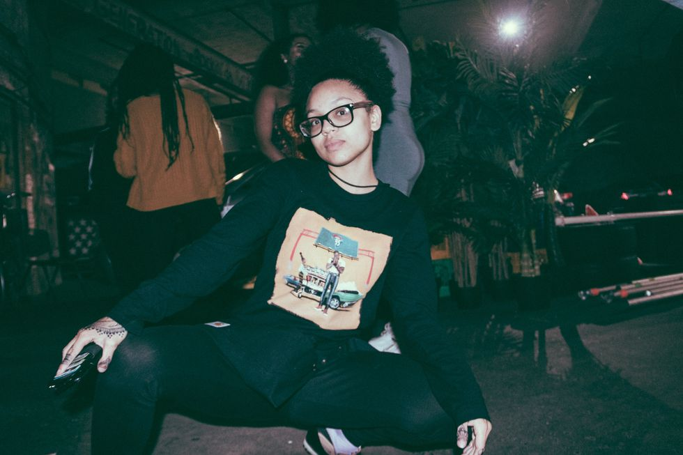 "Model wears Jidenna's ""85 to Africa"" longsleeve T-shirt backstage while doing a rap squat."
