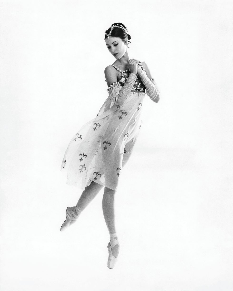 A young Kain in a flowy transparent dress with a pattern and details at the top. She has her hair up in a headpiece. She clutches her hands together, is up on pointe on one foot and has the other leg behind her in a tiny arabesque. She looks down towards her foot