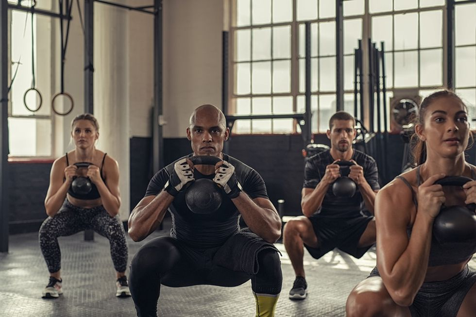 A group of men and women exercising in a gym.