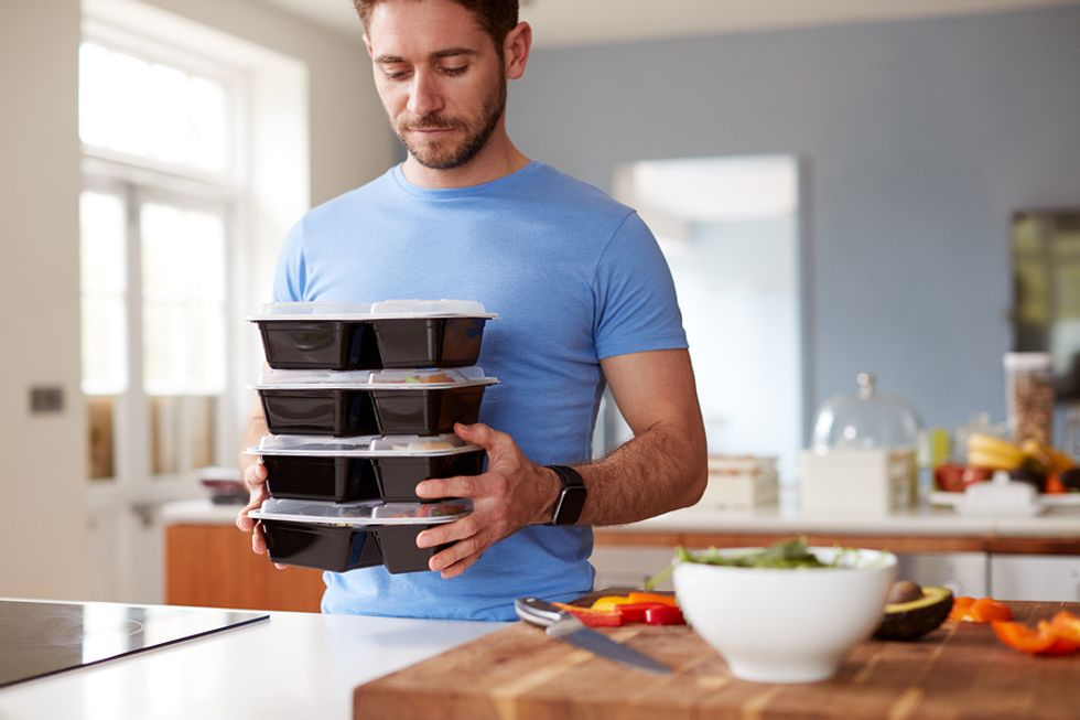 Young professional man preparing healthy meals after being laid off from his job.