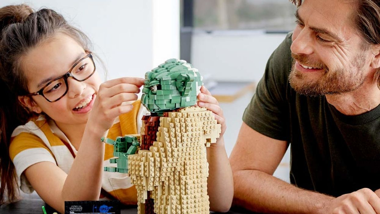 Little girl and man building Star Wars Yoda figure out of LEGOs