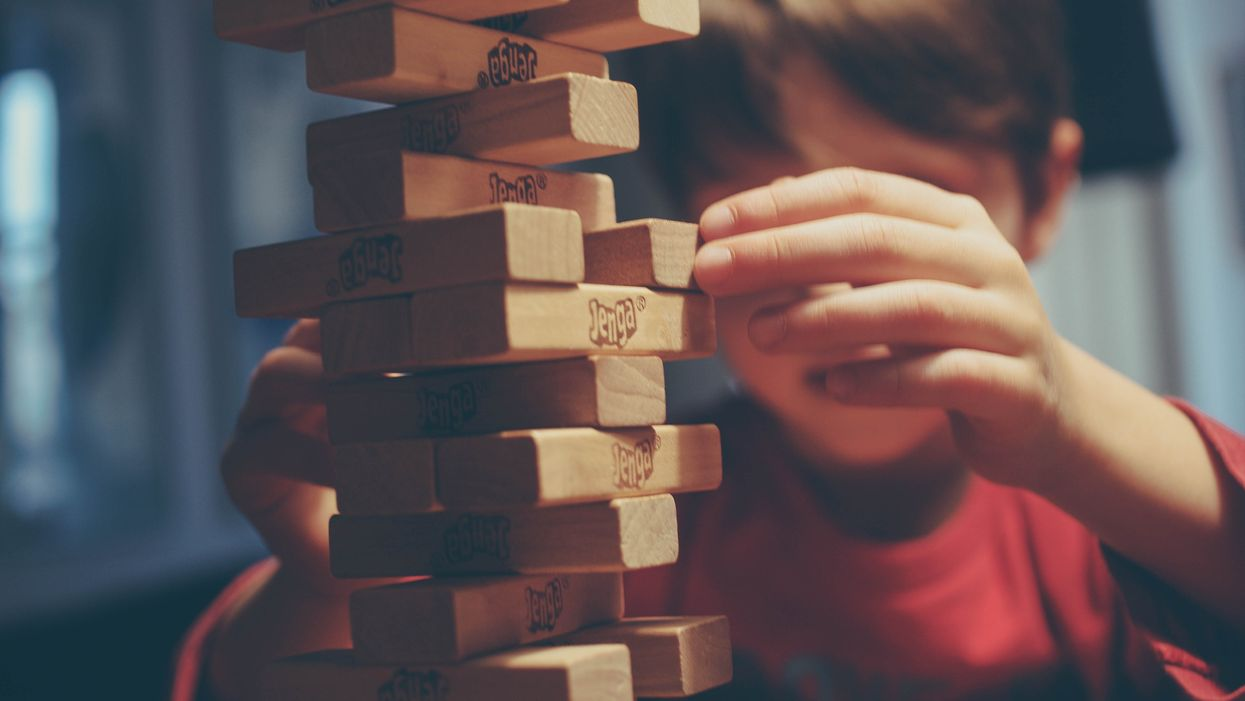 Child playing with a tower of Jenga blocks