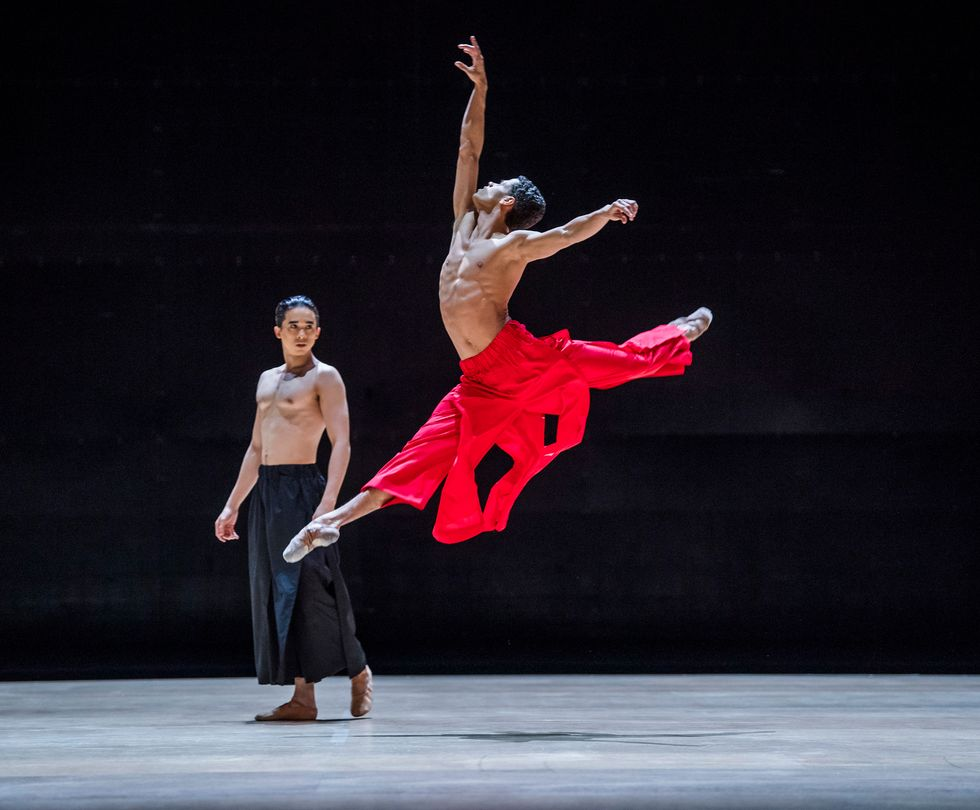 A lean, bare-chested man leaps into the air. His front leg is at a 45 degree angle to the ground, the back one in a perpendicular attitude. His head tips to the ceiling as his right arm reaches gracefully upward, the left outflung to his side. The bright red trousers he wears flare with the motion. Upstage, another man costumed identically but for the black color of his trousers looks on.