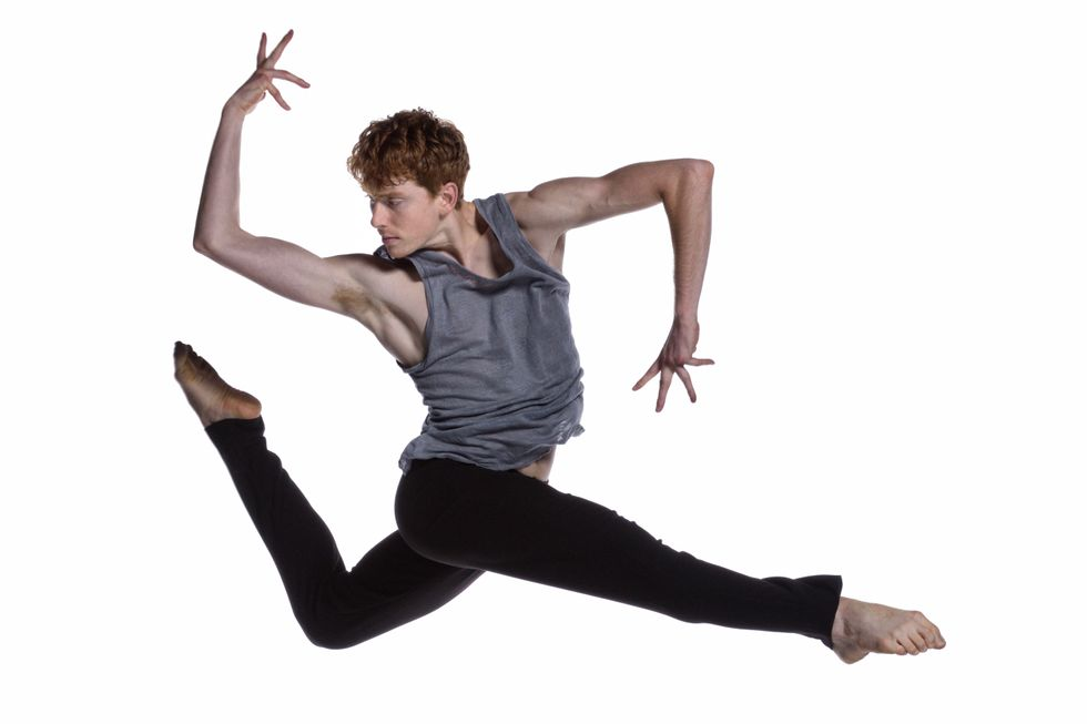 A red-headed male dancer leaps. His right leg crosses straight in front, while his left bends into a parallel attitude behind him. He is twisted toward his back leg, elbows bent at 90-degree angles with his back forearm stretching up and front forearm pointed down.