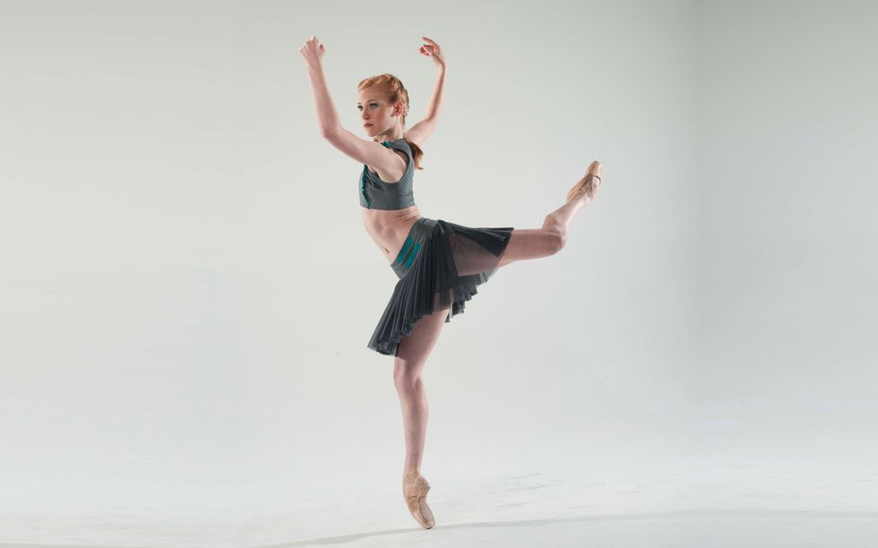A red-headed ballerina balances in a forced arch back attitude en pointe. Her arms are bent at the elbows and in slight opposition to the twist of her open attitude so her forearms frame her face.