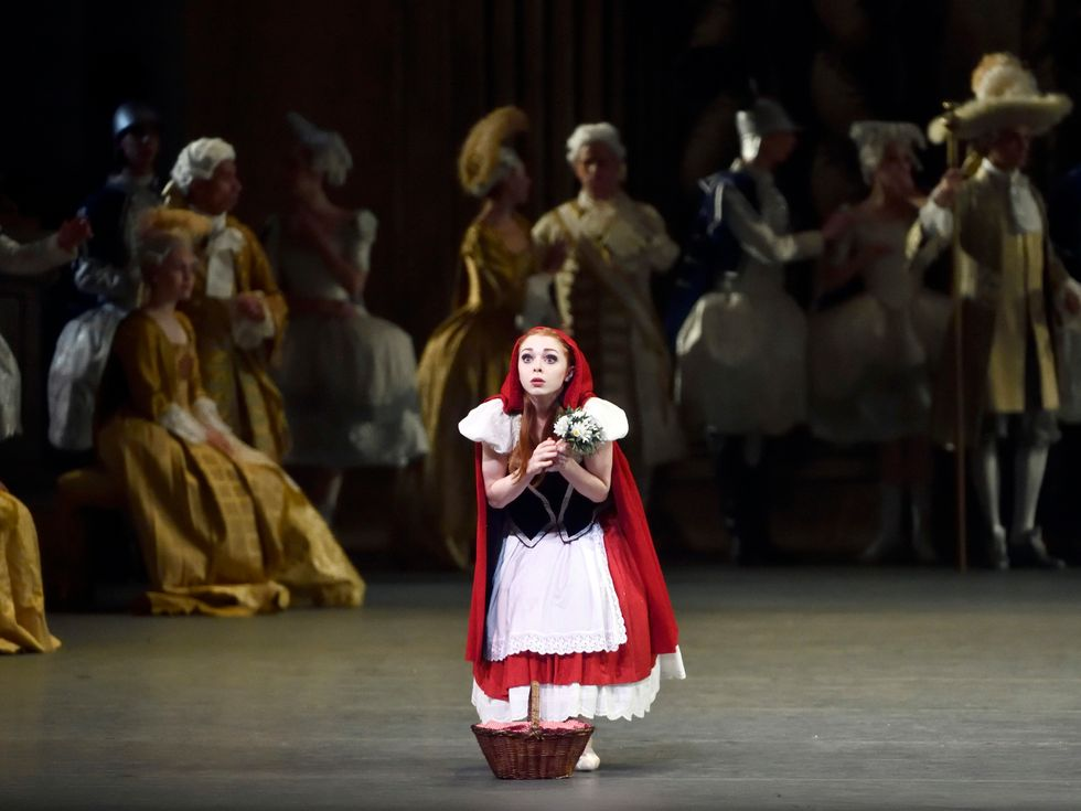 A short, red-headed ballet dancer dressed as Little Red Riding Hood stares out at the audience with wide eyes. She clutches flowers in both hands as she peeks out from beneath her red robe, a wicker basket by her feet.