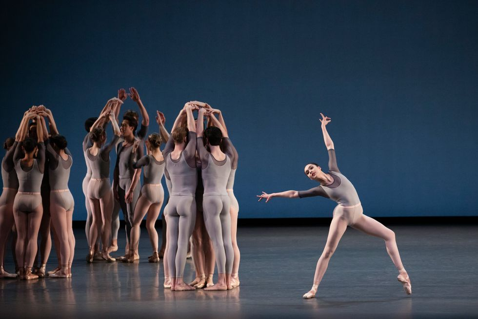 To the left, small groups of dancers dressed in gray leotards and tights (pink for the women, gray for the men) cluster in small circles facing in, hiding a dancer in the center from sight as they clasp their hands overhead. To the right, a long limbed dancer with striking features leans with one pointe-shoe clad foot hovering just above the stage in what is almost an open lunge. She arches toward her back leg as her arms form a slightly over-extended 'V' above her shoulders.
