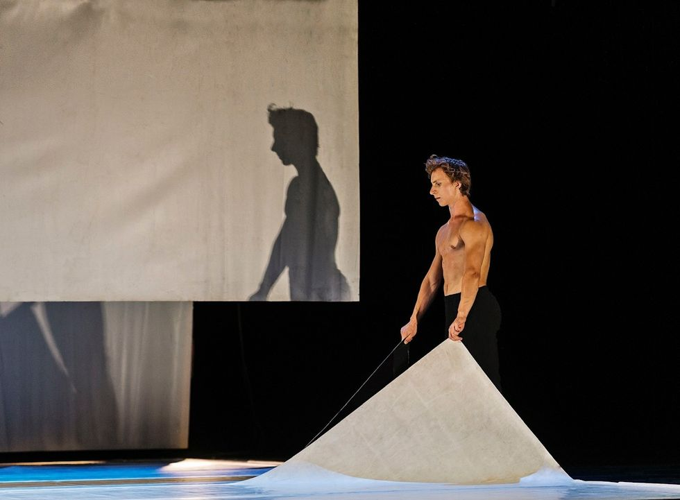 A bare-chested male dancer lifts the corners of two panels of marley, arms raised slightly in front of his sides. His shadow is cast on a piece of fabric just upstage.