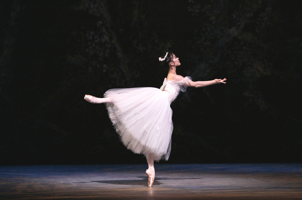 A smiling ballerina dressed in a white romantic tutu balances in an open arabesque. She is oriented to the side of the stage, her arms stretched before her with palms facing up, as though offering something.