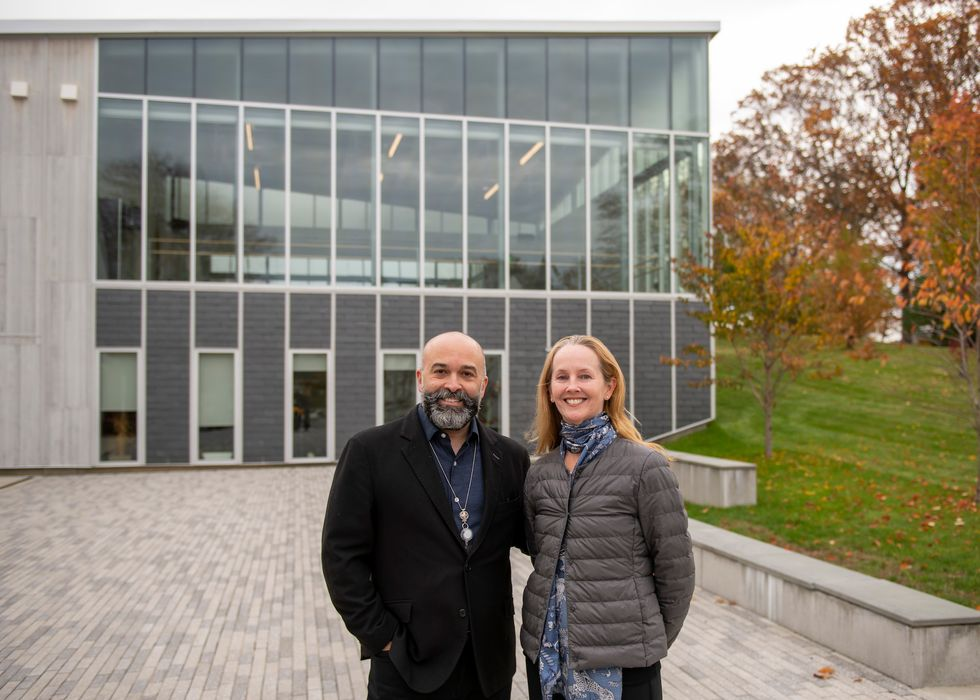Antonio Vivo and Margaret Tracey, wearing jackets, pose standing next to each other outside a school building.