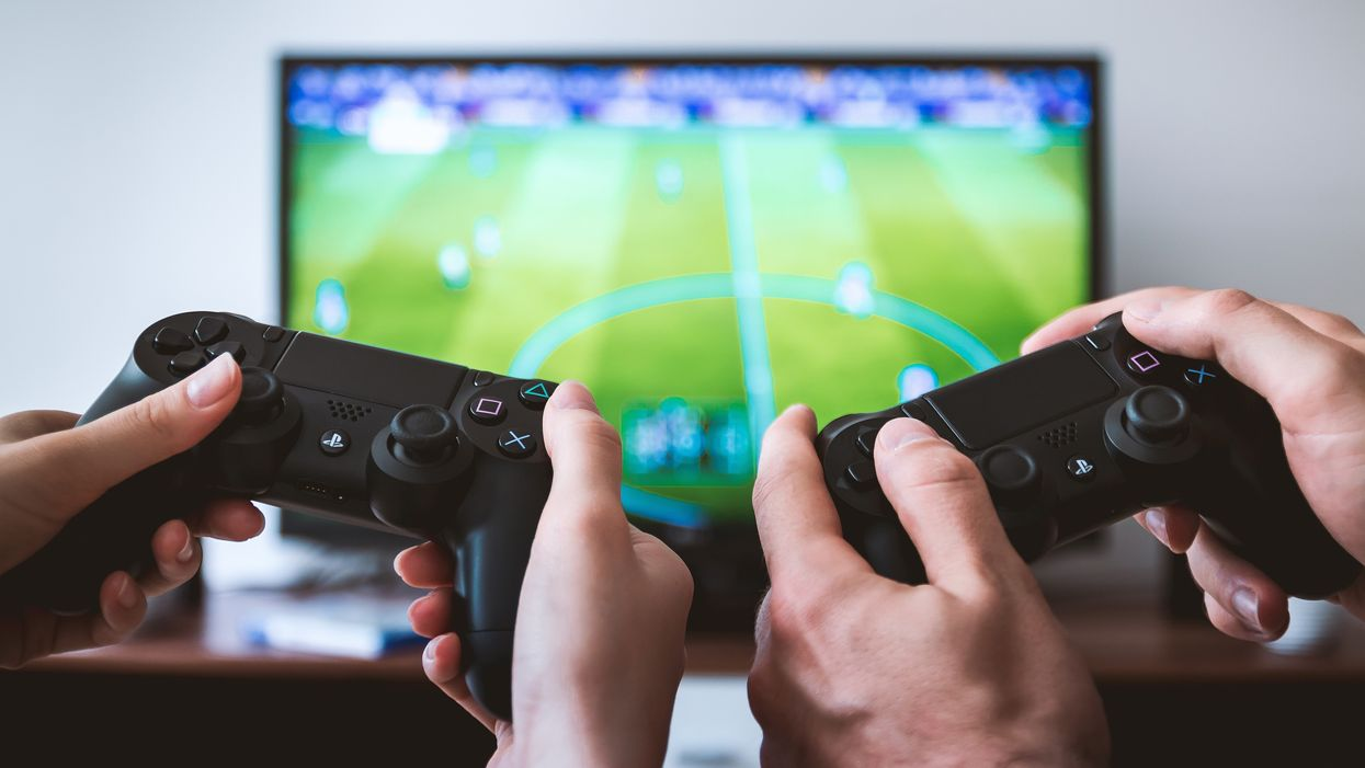 Couple holding game controllers in front of television