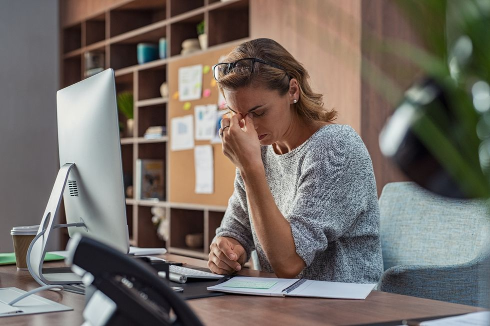 Woman sitting at her desk stressed about her career future in the recession