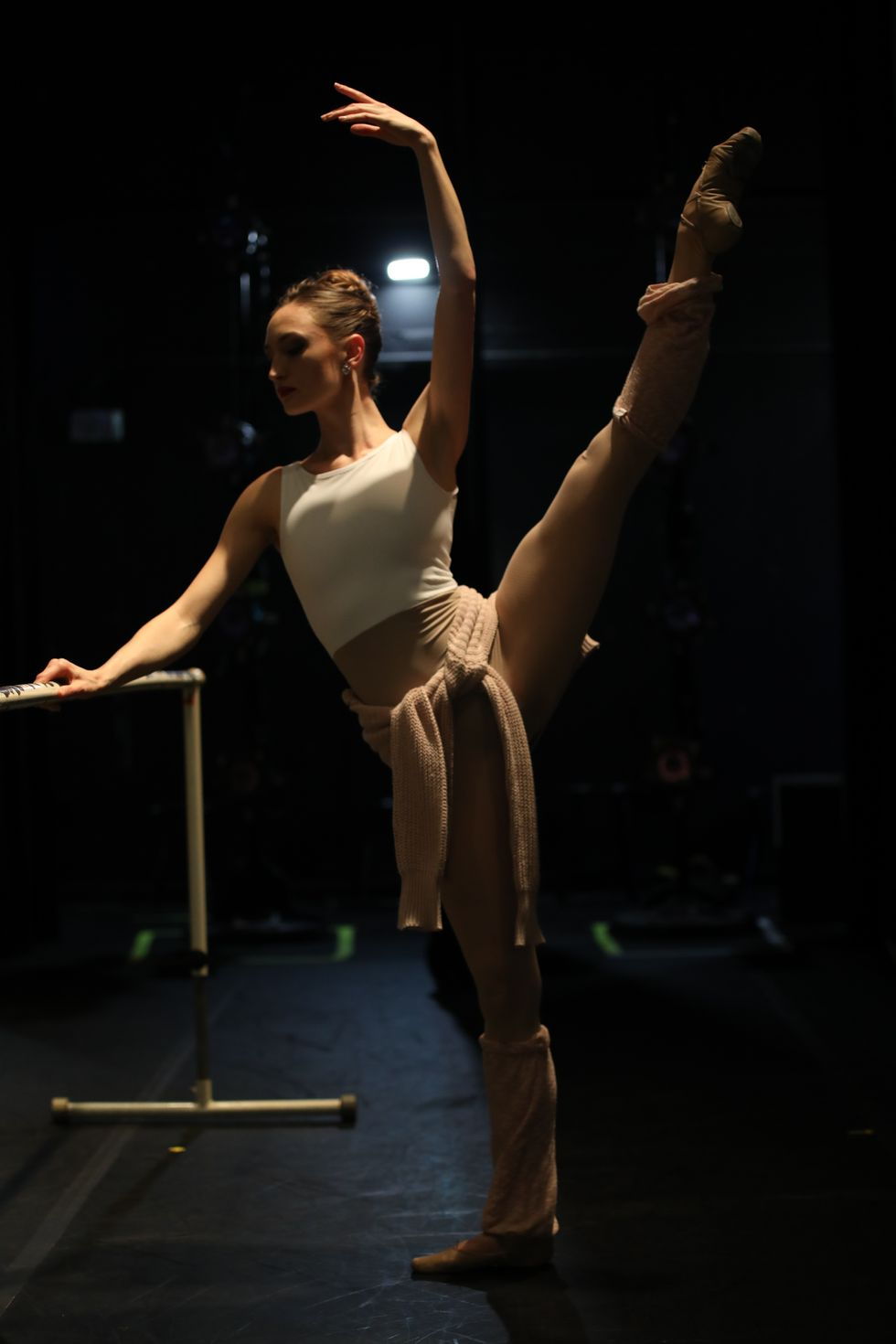 A ballerina warms up at a barre backstage.