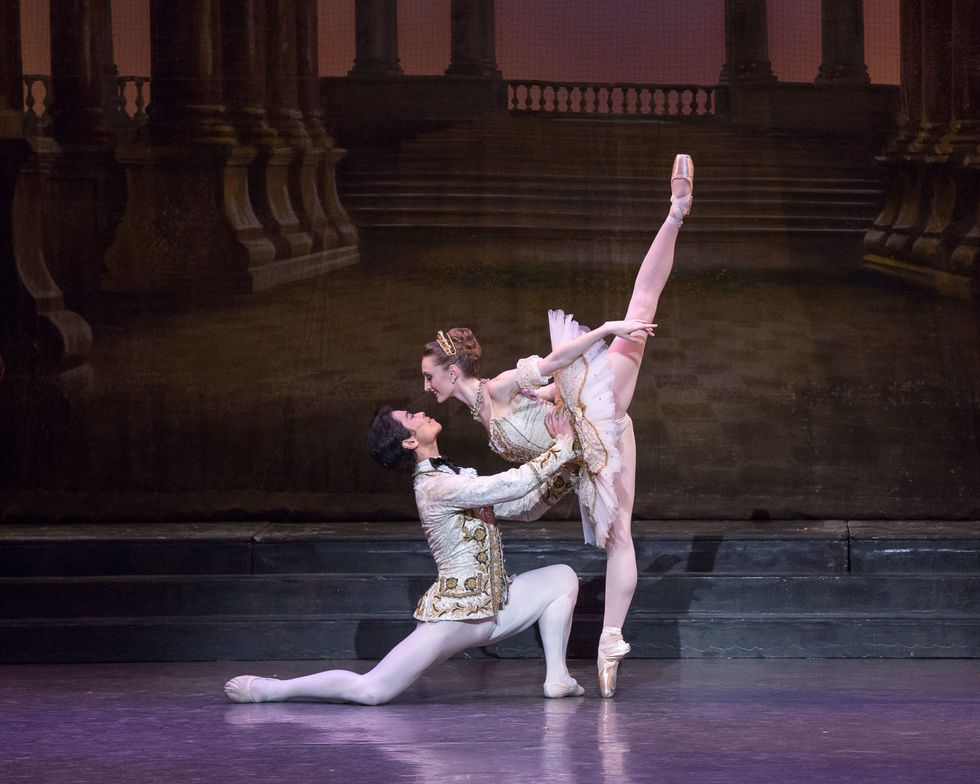 A male and female ballet dancer pose together onstage. The male , wearing a prince costume, is on his knee holding the waist of the ballerina, who wears a tutu and leans forward toward him on pointe.
