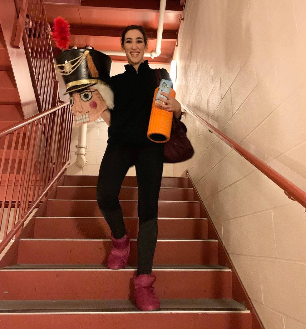 Dafoe walks down stairs, while wearing warm-up clothes and holding the Nutcracker head.