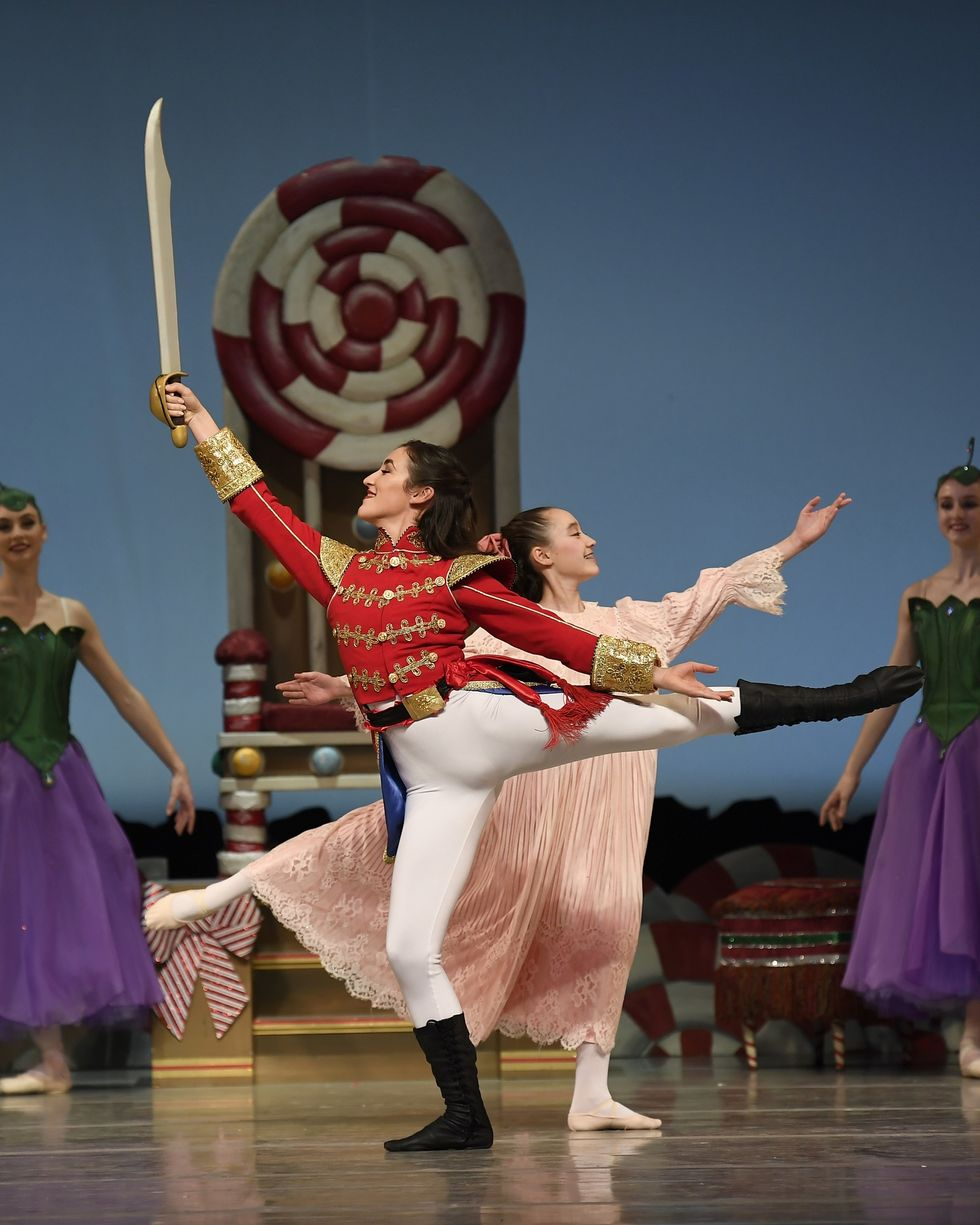A performance image of the Nutcracker in front of Clara. Each are doing an arabesque in an opposite direction of the other.