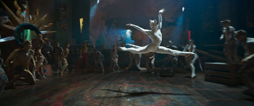 Francesca Hayward in a white cat costume leaps across a wooden floor. She's surrounded my a number of cats.