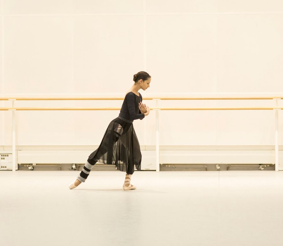 In a black leotard and long black skirt, pointe shoes and striped legwarmers, Francesca Haywards leans forward in a back tendu.