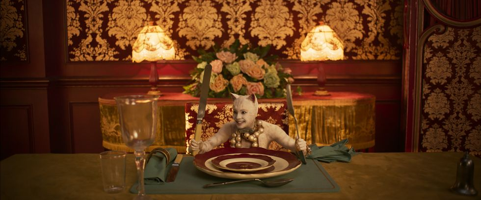 Francesca Hayward in a white cat costume sits at a giant, ornate table holding a huge fork and knife.