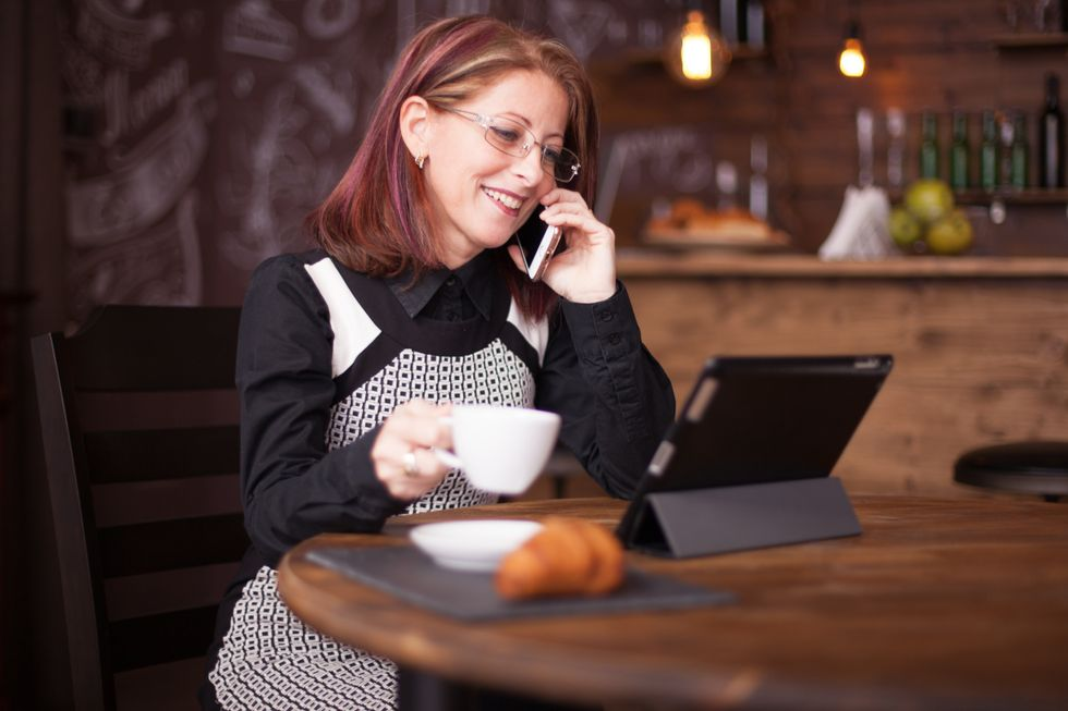 smiling businesswoman while talking on the phone in front of tablet
