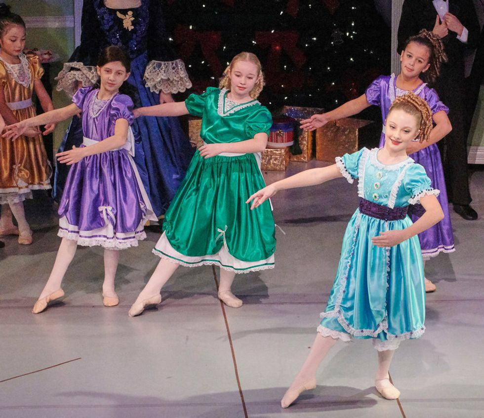 A stage photo of Nutcracker of four young girls dressed in colorful party dresses and soft shoes. Stella DiPasquale wears a purple dress and a brown wig.