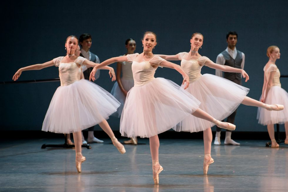 Three female Boston Ballet students pose in arabesque onstage, wearing long white tutus.