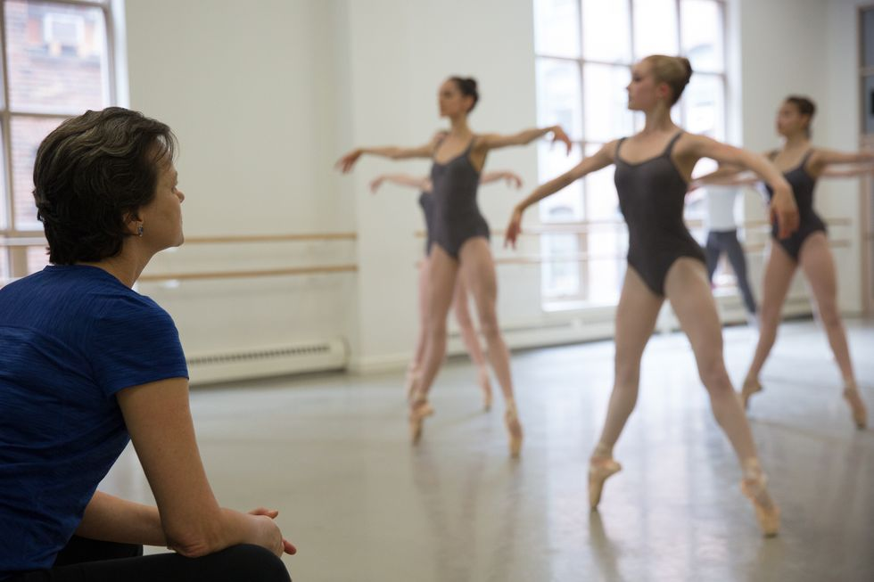 A teacher watches as four female students in gray leotards \u00e9chapp\u00e9 on pointe.