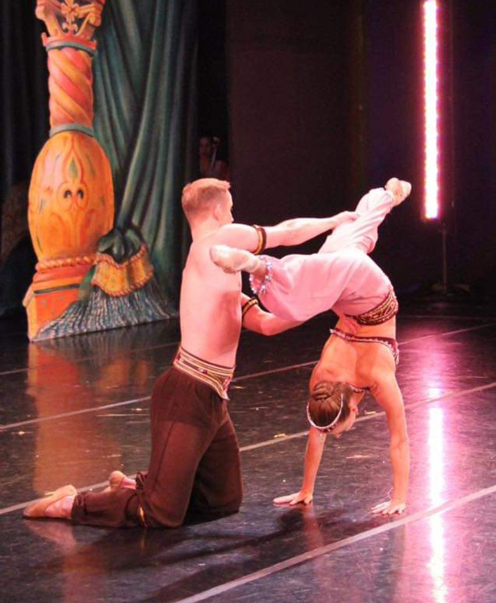 Luke Joiner helps Jennifer Goodman with a back walkover onstage during a Nutcracker performance. They both wear harem pants, and Goodman wears a sparkly top.