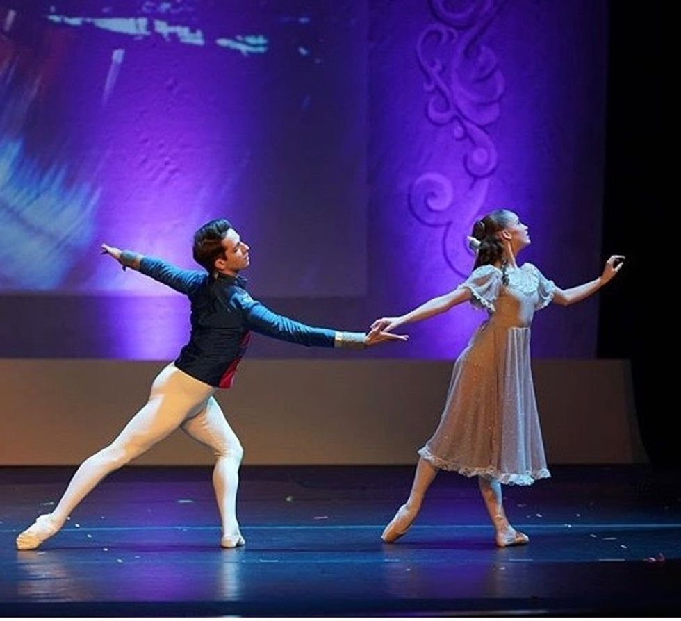 Michael Breeden, in a blue jacket and white tights, reaches for his partner's right hand during a performance.