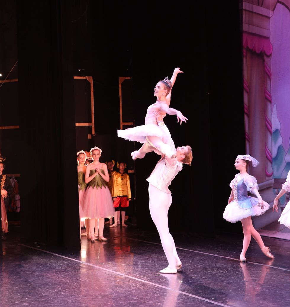Evan Swensen lifts Savannah Lowrey high into the air during a Nutrcacker performance. She wears a pink tutu, tiara and pointe shoes, he wears a white jacket and tights.