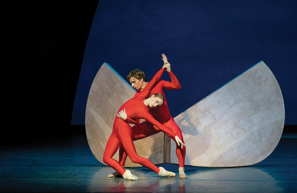 Bell and Hurlin in right unitards against a structural backdrop onstage.