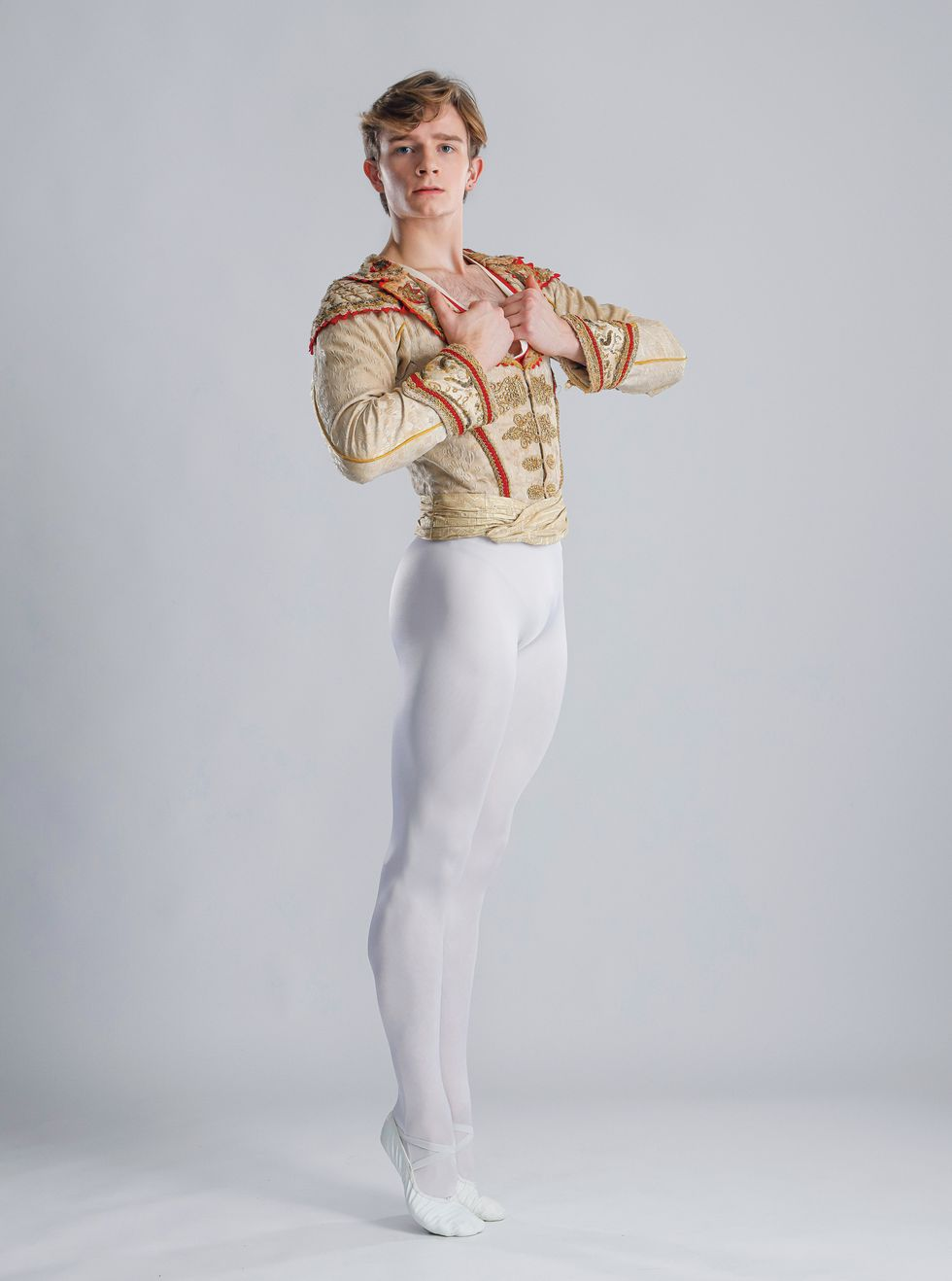 Aran Bell poses against a light grey background. He's wearing white tights and shoes and a gold and Don Quixote jacket.