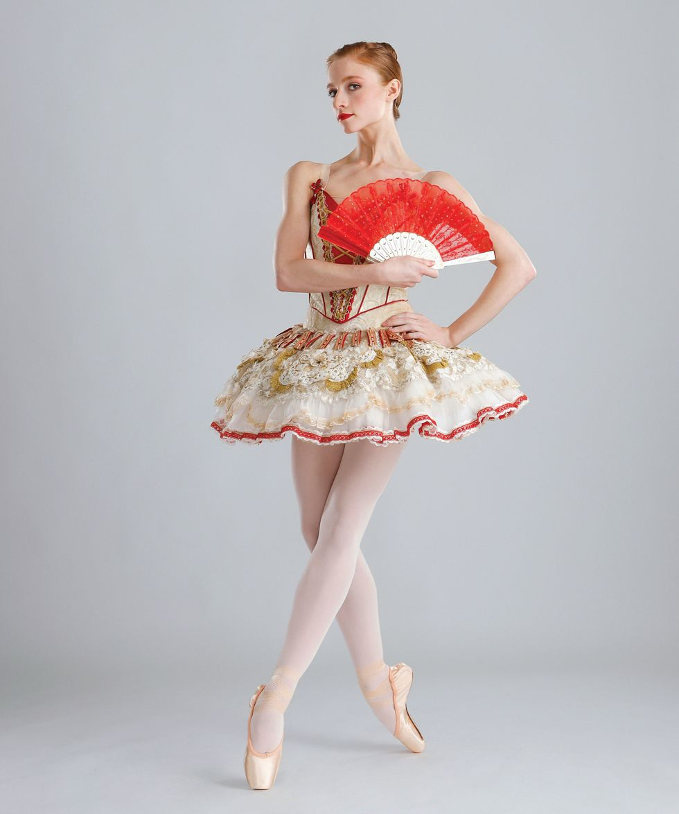 Catherine Hurlin poses with a red fan against a light grey background. She's wearing a red and gold Don Quixote tutu and pointe shoes.