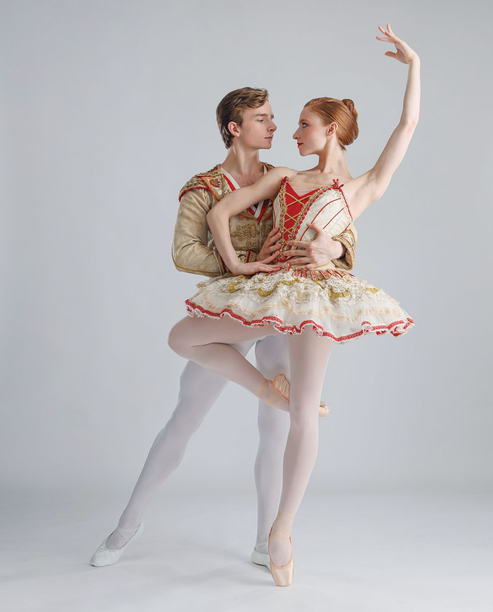 Bell and Hurlin pose against a light grey background dressed in red and gold Don Quixote costumes.
