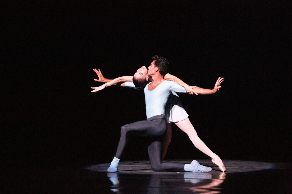Renan Cerdeiro, in black tights and a blue shirt, knees on his right knee with arms outstretched as Katia Carranza bends backwards over them.