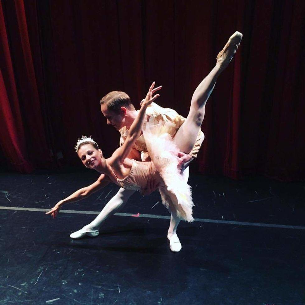 """Luke Joiner lifts Jennifer Goodman, who wears a pink tutu,  into a """"fish"""" lift backstage."""