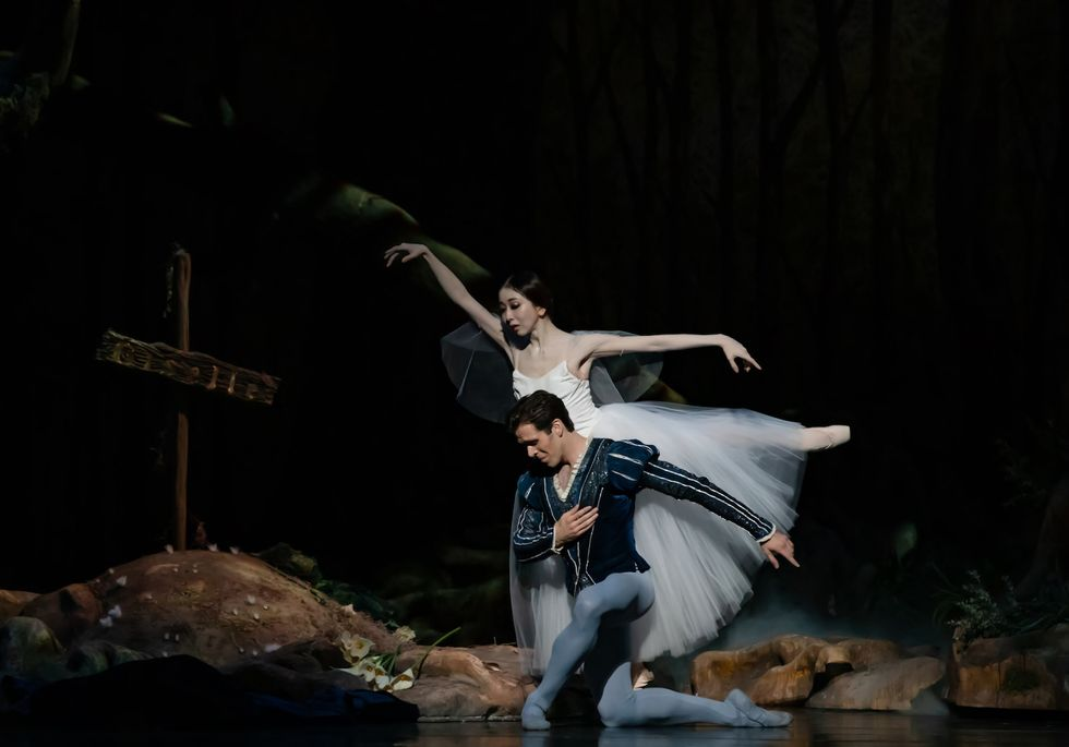 Yuriko Kajiya, wearing a white Romantic tutu, balances in arabesque behind a kneeling Connor Walsh. He wears a dark blue jacket and light blue tights.