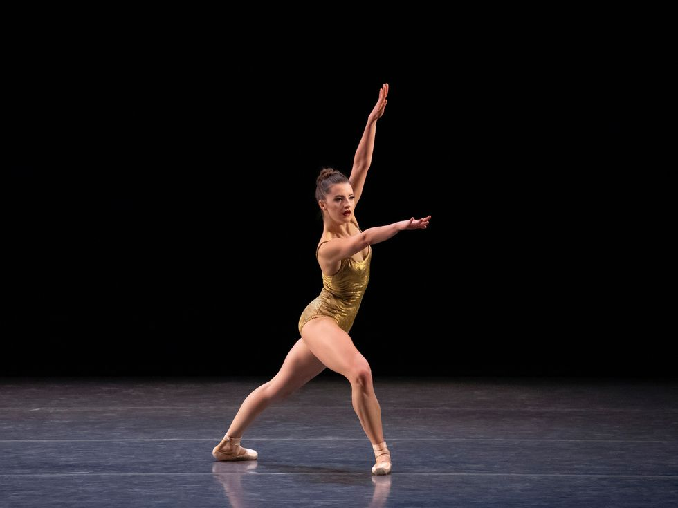 Indiana Woodward wears a gold leotard and stands in a large fourth position lunge onstage.