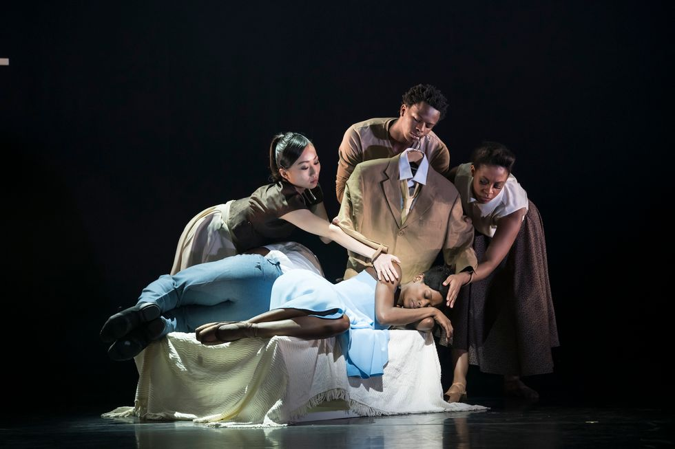 Three dancers hold a brown suit and lean over Cira Robinson as she sleeps onstage.