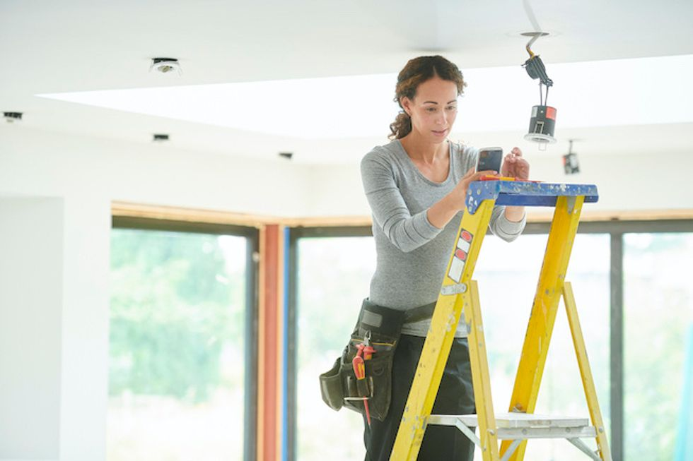 Electrician with smartphone installing a device on the ceiling in a house