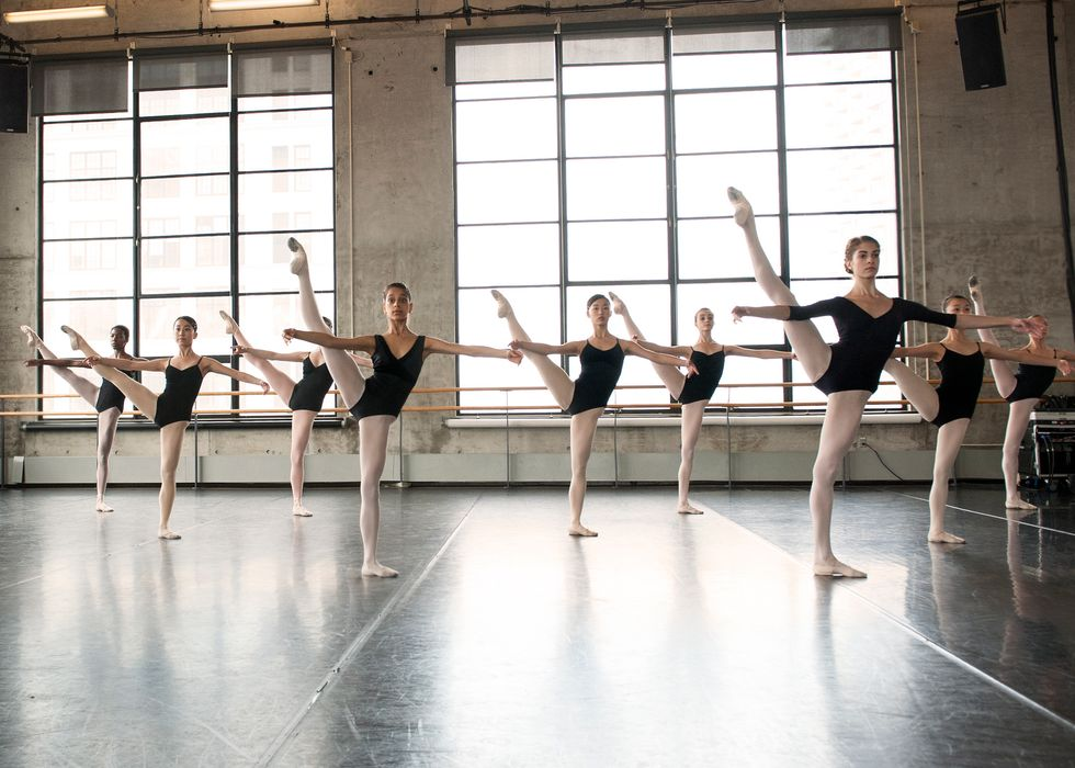 A class of young women in a brightly lit studio with large windows. They have one leg in a la seconde, and their arms in second.