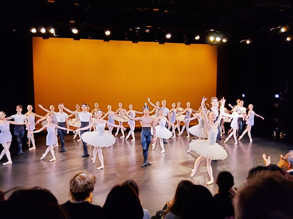 A curtain call for a performance, of dozens of students in various costumes.